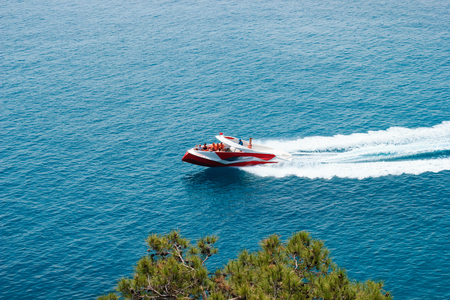 KEMER, TURKEY - MAY 2017: Motor boat with tourists moving with with high speed leaving trail in water Redakční
