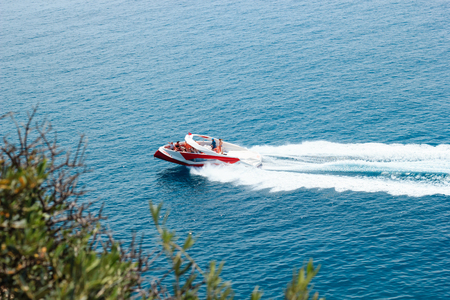 KEMER, TURKEY - MAY 2017: Motor boat with tourists moving with high speed leaving trail in water Redakční