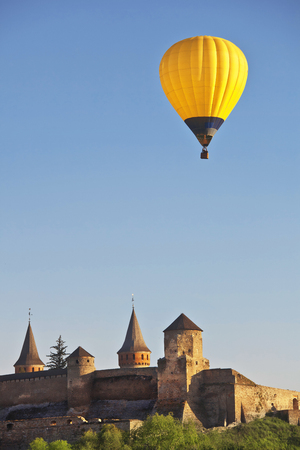yellow colorful hot air balloon flying in blue sky over roofs of city castle Фото со стока