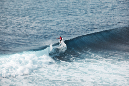 Surfer in ocean on big waves. Bali surfing aerial shot. water sports. Healthy Active Lifestyle. Surfing. Summer Vacation. Extreme Sport.