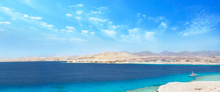 seascape large wide panorama with desert mountains, bay with ships, sunny blue sky, nobody