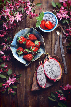 flatlay food background - empty dark wooden board with dragon fruit, strawberries, fresh smoothie and pink flowers, copy space for text