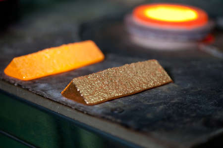 closeup picture of ingots of melt gold, hot shiny metal bars on table and fire furnace on background, nobody Imagens