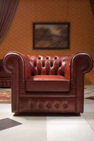 empty interior living room background in warm colors decorated with classic luxury leather soft chair and painting on the wall, nobody