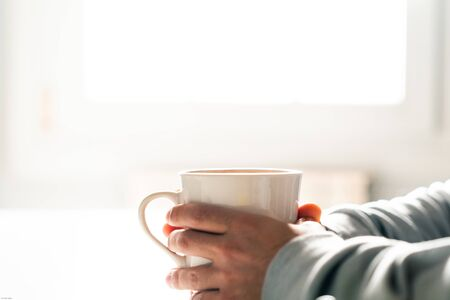 Person warming their hands with a hot cup of coffee. Holding a cup. Stock Photo