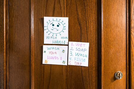 Drawings by a child of positive messages for the coronavirus hanging on the bathroom door. Wash your hands.