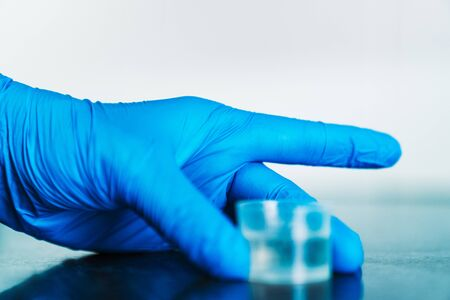 Hand with a blue latex glove holding a measuring cup full of disinfectant. Foto de archivo