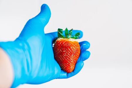 Hand holding a strawberry with blue latex gloves. Disinfecting the fruit to prevent the spread of the coronavirus. 스톡 콘텐츠