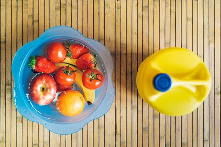 Basin with different fresh and clean fruits on a wooden base. Reklamní fotografie