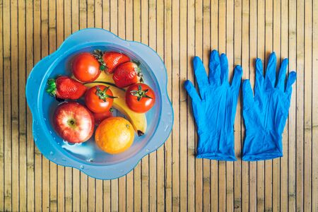 Blue bowl with different fresh and clean fruits on a wooden base with blue latex gloves. Bananas, tomatoes, apples, strawberries and oranges immersed in water with lye.
