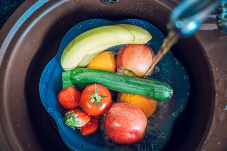 Blue basin full of fruits and vegetables with tap water in the kitchen sink. Disinfecting fruits and vegetables to prevent the spread of the coronavirus.