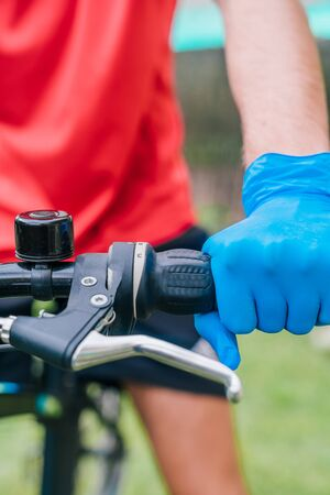 Person holding the handlebars of the bicycle with blue latex gloves as a preventive measure against the coronavirus. Cyclist riding a bike outdoors in the park.