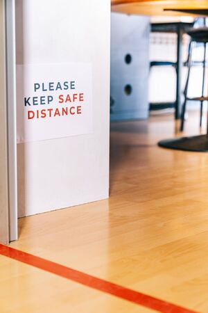 Please keep safe distance. Waiting behind a red line to enter a classroom. Social distancing measures for the reopening and adaptation of schools and academies to the new normal. Stock Photo