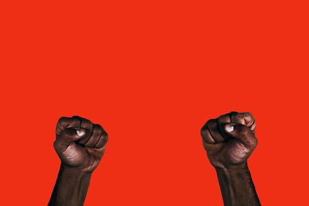 Powerful black fists raised calling for freedom and equality on a red background. Foto de archivo