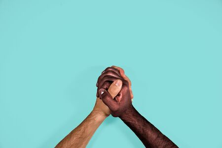 Multicultural hands united calling for freedom and equality on a blue background. African black hand and caucasian white hand together calling for stop racism.