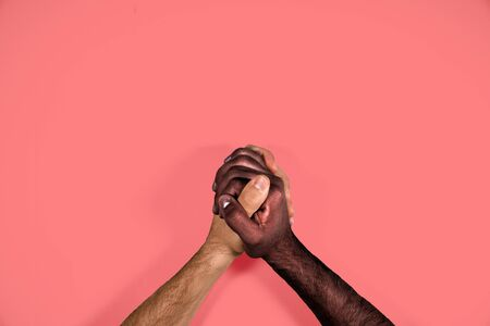 Multicultural hands united calling for freedom and equality on a red background. African black hand and caucasian white hand together calling for stop racism. Stock Photo