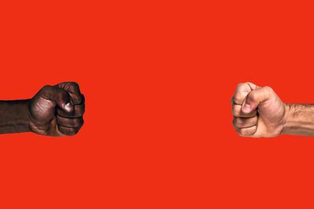 Multicultural fists raised. African black fist and caucasian white fist raised calling for freedom and equality on a red background. Stock fotó