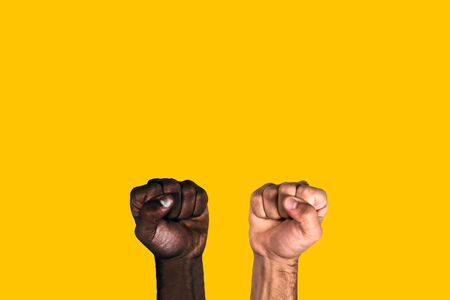 African black fist and caucasian white fist raised calling for freedom and equality on a yellow background. Multicultural fists raised.
