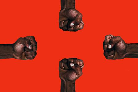 Powerful african black fists raised calling for freedom and equality on a red background. Foto de archivo