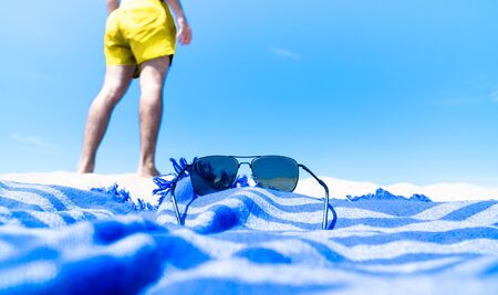 Person enjoying the summer beach holiday wearing a yellow swimsuit, blue beach towel and sunglasses on the sandy beach on a sunny day.
