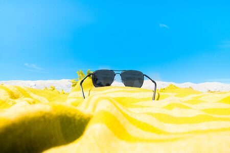 Yellow beach towel and sunglasses on sandy beach in a sunny day. Concept summer beach holiday. Banque d'images
