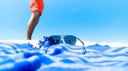 Person enjoying the summer beach holiday wearing a red swimsuit, blue beach towel and sunglasses on the sandy beach on a sunny day.