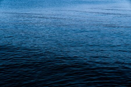 Background of a calm blue sea with the texture of the waves in the blue hour at sundown. Concept of climate crisis and refugee crisis in the Mediterranean Sea.