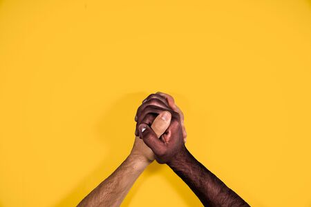 Multicultural hands united calling for freedom and equality on a yellow background. African and caucasian hands together calling for stop racism.