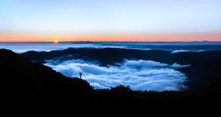 Traveler escaping in solitude into the wilderness. Silhouette of an adventurous person with his hands raised contemplating an immense landscape at sunset. Connection to nature to the great outdoors. Reklamní fotografie