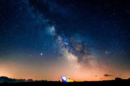 Tents glowing under the milky way at night. Camping in the mountains under the starry magical sky. 5 Billion Star Hotel.