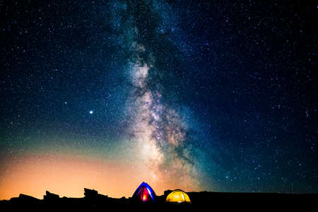Tents glowing under the milky way at night. Camping in the mountains under the starry magical sky. Camping and wild life concept. Real outdoor adventure. Banque d'images