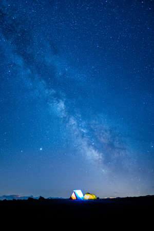 Two camping tents glowing under the milky way at night. Camping in the mountains under the starry magical sky. 5 Billion Star Hotel. Banque d'images