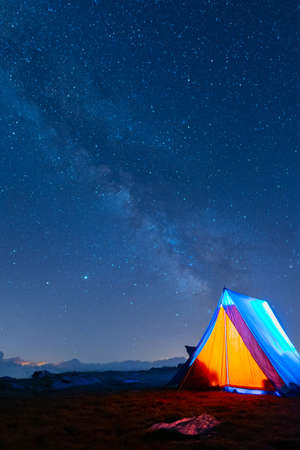 Ridge tent glowing under the milky way at night. Camping in the mountains under the starry magical sky. 5 Billion Star Hotel. Banque d'images