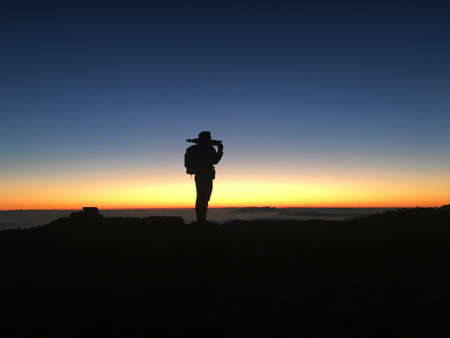 Photographer contemplating the landscape. Silhouette of a mountaineer on top of the mountain at sunset or sunrise. Traveler exploring new places and escaping in solitude into the wilderness.