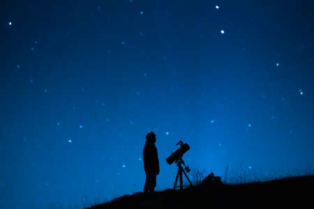 Astronomer observing the immensity of the universe and the stars. Silhouette of an astronomy lover person with a telescope observing the blue starry sky at night.