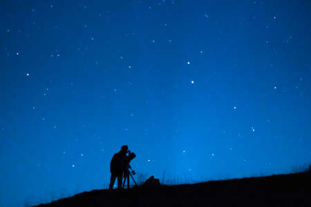 Silhouette of an astronomer observing the immensity of the universe and the stars. Astronomy lover with a telescope observing the blue starry sky at night.
