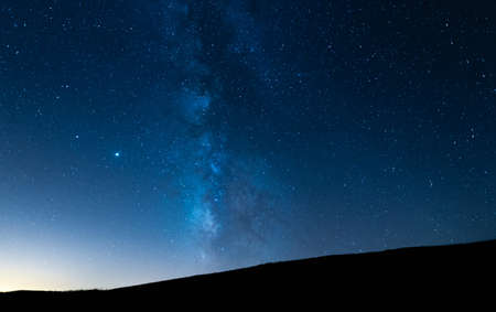 Milky way up a hill in a starry night sky. Blue sky with stars without light pollution.