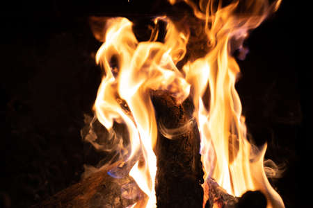 Logs of firewood burning in bright and powerful orange flames in a fireplace. Detail shot of the fire. 版權商用圖片