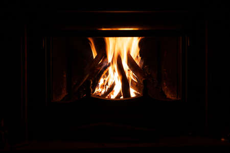 Fireplace with logs of firewood burning in bright orange flames.