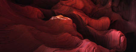 Amazing sandstone formations inside a caves in famous Grand Canyon and Antelope Canyon, USA. Vibrant red colors of eroded rock. Abstract wave forms texture.