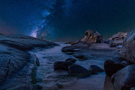 Sea landscape at night with milky way, stars and curious shapes rocks. Beautiful starry maritime panorama in beach of Cala de Roques Planes, in Playa de Aro, Costa Brava, Girona, Catalonia, Spain.