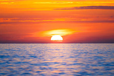 Sun rising in the sea. Beautiful sunrise on the ocean with a big and colorful sun in summer. A new day begins.