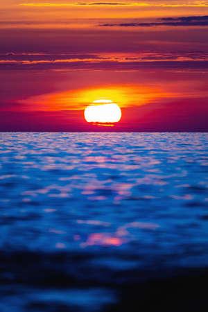 Colorful sunset with large bright sun under the sea surface. Sea sunset, ocean sunrise, seascape.