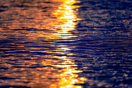 Sea waves texture with sunset or sunrise light reflecting on the water. Sunbeams illuminate the blue ocean water with warm orange light. Closeup view. Artistic and creative nature background. 免版税图像