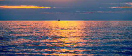 Boat in the middle of the sea at sunrise or sunset with the golden waves of the warm color of the sun. Lone fisherman going out to fish in the ocean in the morning. Vacation, relaxation, tranquility.
