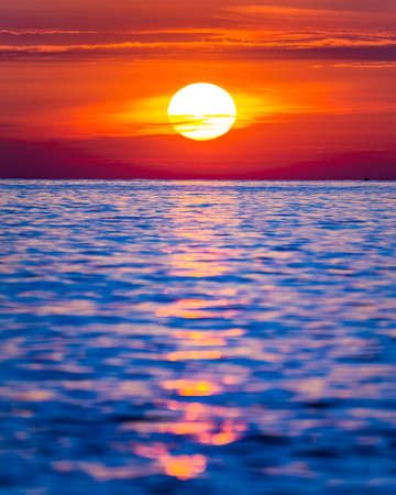 Bright sunset with large yellow sun under the sea surface.