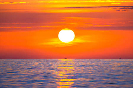 Sun rising in the sea with a fishing boat in the rays of the sun above the waves. Beautiful sunrise on the ocean with a big and colorful sun in summer. A new day begins. 免版税图像