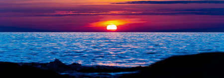 Panorama of sea sunset, ocean sunrise, seascape. Colorful sunset with large bright sun under the sea surface.