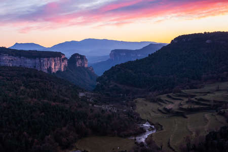 Landscape of a valley with towering rocky mountains with a beautiful sky with pink and orange clouds at sunset. Cingles de Tavertet, Collsacabra, Osona, Barcelona, Catalonia, Spain. 免版税图像