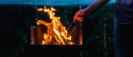 Anonymous person stirring the embers of the barbecue. Preparing the fire for an outdoor barbecue at night. 免版税图像